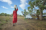 Rachel Abuk carries water in a camp for displaced people in Melijo, South Sudan, near that country's border with Uganda. It's a one-hour walk from the existing water site to her tent. Families here fled fighting around Bor, in Jonglei State, in December 2013, but have not been warmly welcomed to this region of Eastern Equatoria State, where two earlier waves of displaced people in the 1980s and 1990s have left relations tense between the newcomers, who are Dinka, and the largely Ma'adi residents around the city of Nimule. The ACT Alliance is helping the displaced families and the host communities affected by their presence, including with the drilling of a new well, and is supporting efforts to reconcile the two groups.