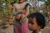 """Cambodia - Kampong Speu Province - Louv Veoun, 39, holding the only duck she has in her garden, her family has become so poor after she lost her land that their daily meal consist of a handful of rice per person at night. """"I don't want money, I want my old land back. It is the land of my ancestors"""". Louv Veoun, 39 and mother of 8, was living in a small cottage on her rice field in Kork until March 2010, when she was dispossesed of her two hectares of land and compensated with 25 USD. She was forced to abandon her house and settle in a piece of land belonging to some of her relatives, close to the plantation. Today, she lives in utter poverty together with her family."""