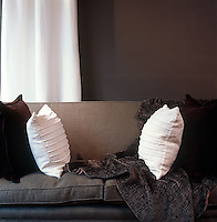 Pin-tucking on a pair of white linen cushions on the sofa in the living room strikes a contrasting note in a masculine room of browns and cream