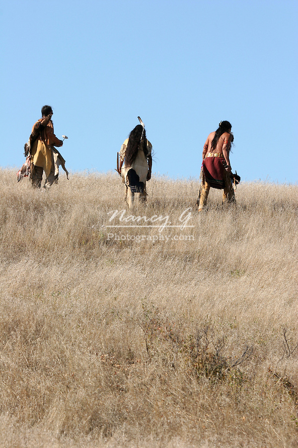 Three Native American Indian men walking uphill in the dry grasses of the prairie of South Dakota