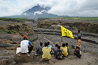 Local villagers looking towards Gunung Merapi and the Gendol River gorge, created during the eruption in November 2010, Kaliadem, nr Yogyakarta, Java, Indonesia.