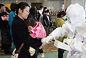 March 17, 2011, Koriyama, Japan - Medical staff in protective gear check radiation levels on local residents in Koriyama, Fukushima prefecture, on Tuesday, March 15, 2011. A nuclear power plant, located along the Pacific coast some 65km southeast of Koriyama, has had a series of trouble in its reactors since a magnitude 9.0 earthquake hit northeastern Japan on March 11. (Photo by AFLO) [3609] -mis-