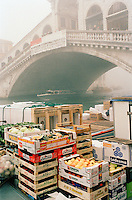 Fresh food produce stacked on a misty morning at the Ponte di Rialto, the Rialto Bridge, Venice, Italy