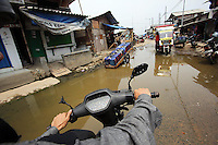 A man drives a motorbike through a flooded area of the port in Jakarta<br />
