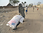 A displaced woman carries home grain in a wheel barrow in Agok, a town in the contested Abyei region where tens of thousands of people fled in 2011 after an attack by soldiers and militias from the northern Republic of Sudan on most parts of Abyei. Although the 2005 Comprehensive Peace Agreement called for residents of Abyei--which sits on the border between Sudan and South Sudan--to hold a referendum on whether they wanted to align with the north or the newly independent South Sudan, the government in Khartoum and northern-backed Misseriya nomads, excluded from voting as they only live part of the year in Abyei, blocked the vote and attacked the majority Dinka Ngok population. The African Union has proposed a new peace plan, including a referendum to be held in October 2013, but it has been rejected by the Misseriya and Khartoum. The Catholic parish of Abyei, with support from Caritas South Sudan and other international church partners, has maintained its pastoral presence among the displaced and assisted them with food, shelter, and other relief supplies.