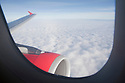 A jet engine and wing viewed from an airplane window. The plane is Airbus A320 by AirAsia airlines.