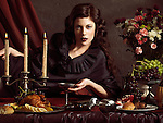High fashion photo of a beautiful woman lying on a table with remains of a festive dinner