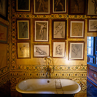A collection of antique prints of male figures by various artists adorn the inlaid walls of this bathroom