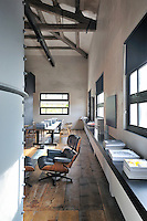 A functional, industrial space with exposed roof beams and a wood floor. An Eames recliner stands next to a long low unit which runs along the length of one wall.