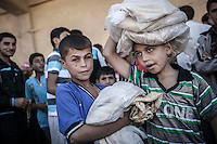 Syrian kids queue for bread at a bakery in downtown Manbij, a city located at the northeast of Aleppo province.