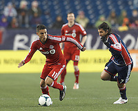 Toronto FC forward Luis Silva (11) looks to pass as New England Revolution midfielder Juan Carlos Toja (7) closes. In a Major League Soccer (MLS) match, the New England Revolution (blue) defeated Toronto FC (red), 2-0, at Gillette Stadium on May 25, 2013.