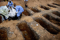 A burial team, at the King Tom cemetery, lower the body of a person who is suspected to have died from ebola into one of a group of pre-dug graves. Due to the rapid increase in burials the cemetery is being enlarged and parts of a nearby rubbish dump is also being used to bury the dead.
