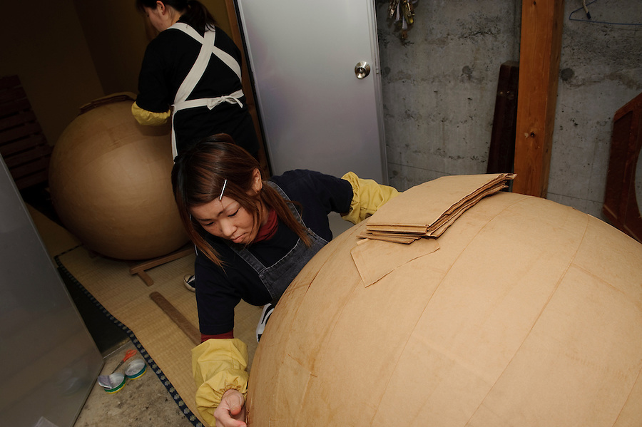 "A worker adds a layer of paper to a ""yonshakudama"" 420kg firework made by Katakai Fireworks Co., Ltd, Katakai, Japan, April 6, 2009. The company makes the world's largest firework, a 120cm round shell called a ""yonshakudama""."