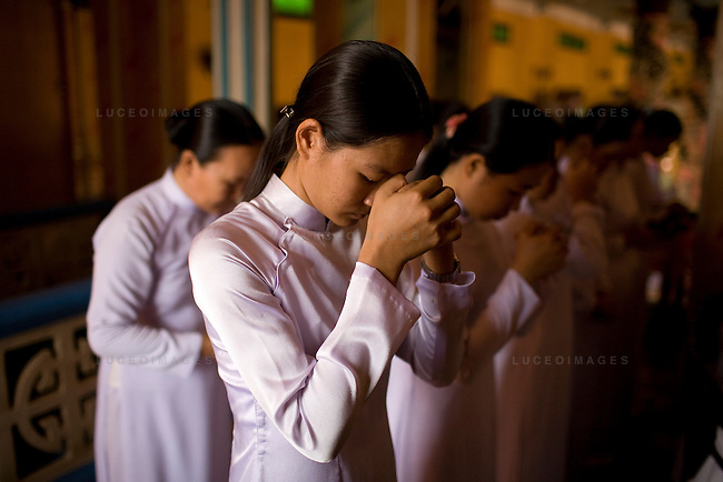 Followers of the Cao Dai religion pray during daily ceremony to begin in Tay Ninh, Vietnam.