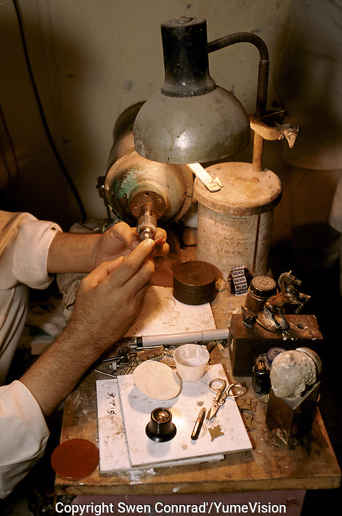 An Afghan forger working on a new coin of Alexander the great for the English market. Peshawar, Pakistan..On the right down, a head of Buddha from the National museum of Kabul Afghanistan, will be copy and sale to the foreign as original for five to height hundred dollars.