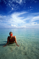 Solitary woman lounging in shallow tropical waters.
