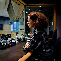 Translator Susan Altenberg seated in a translator's booth at the European Parliament in Brussels. Every month she, along with thousands of other parliamentary staff, travels between the three sites of government in Brussels, Strasbourg and Luxembourg.
