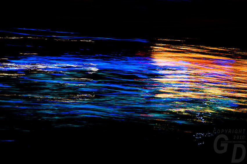 Reflection of a passing boat at night on the Mekong River, Phnom Penh, Cambodia
