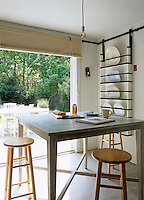 Floor-to-ceiling windows in this kitchen connect the small dining area with the garden
