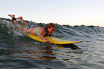 Central America, Costa Rica, Tamarindo. Female surfer paddles into wave in Costa Rica.