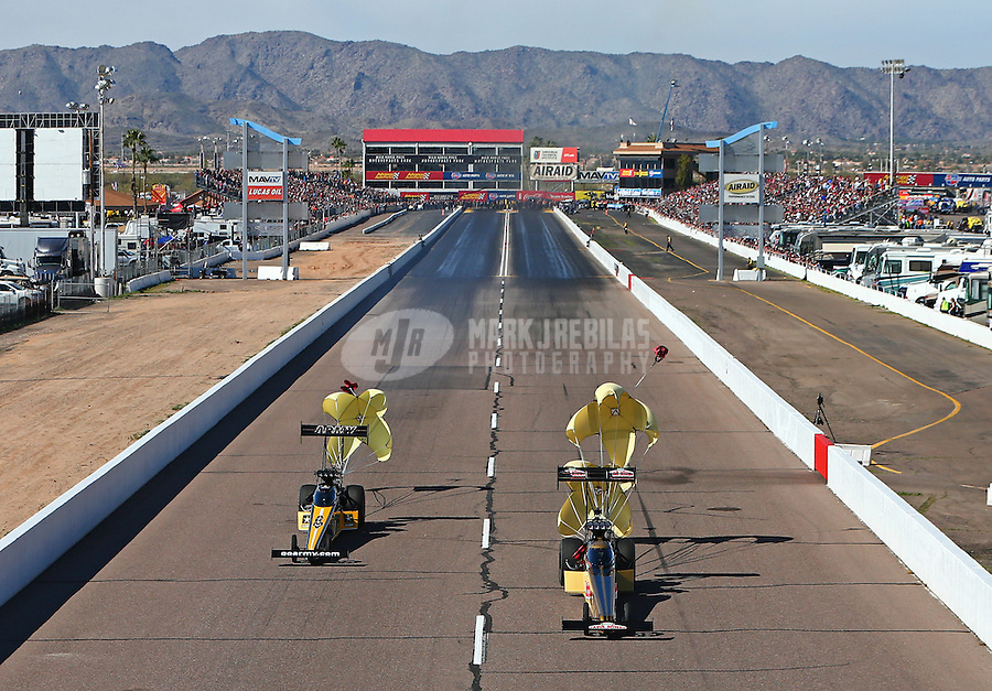 Feb 25, 2017; Chandler, AZ, USA; NHRA top fuel driver Leah Pritchett (right) slows with two parachutes alongside teammate Tony Schumacher during qualifying for the Arizona Nationals at Wild Horse Pass Motorsports Park. Mandatory Credit: Mark J. Rebilas-USA TODAY Sports
