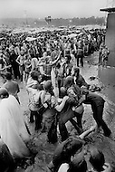 Watkins Glen, NY. July 28th, 1973.<br /> People dancing in the mud during the Summer Jam at Watkins Glen was a 1973 rock festival which once received the Guinness Book of World Records entry for &quot;Largest audience at a pop festival.&quot; An estimated 600,000 rock fans came to the Watkins Glen Grand Prix Raceway outside of Watkins Glen, New York on July 28, 1973, to see The Allman Brothers Band, Grateful Dead and The Band perform.<br /> Similar to the 1969 Woodstock Festival, an enormous traffic jam created chaos for those who attempted to make it to the concert site. Long and narrow country roads forced fans to abandon their vehicles and walk 5&ndash;8 miles on that hot summer day. 150,000 tickets were sold for $10 each, but for all the other people it was a free concert. The crowd was so huge that a large part of the audience was not able to see the stage; however, twelve huge sound amplifiers, installed courtesy of legendary promoter Bill Graham, allowed the audience to at least hear.