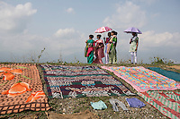 India – West Bengal: Villagers drying up clothes on the slopes of the Diana river at Red Bank Tea Estate, in the Dooars region. The garden, which houses 888 workers out of a population of 5,000 people, has been closed since 2013. With companies obliged to provide workers with houses, discounted food rations, schooling, water and health facilities, closures often leave workers with no assistance, nourishment or money. Thousands of them have died of starvation in the past decade.