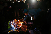A woman place a candle on a memorial set up for John Lennon around the 'Strawberry Fields' in Central Park during the 35-year anniversary of his death in New York December 8, 2015. The death of John Lennon still reverberates as a defining moment for a generation and for the music world. Police said the shooting occurred outside the Dakota, the century-old luxury apartment house where Lennon and his wife, Yoko Ono, lived. It is across the street from Central Park. Kena Betancur/VIEWpress.