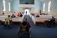 Fernald Developmental Center residents Margaret Rouleau, 84, (from left) Mary Ann Kaufman, 70, and Teresa Kacinski, 46, wait for the service to start in the Chapel of the Holy Innocents in Waltham, Massachusetts, USA.