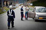 Kawauchi, April 26 2011 -.(eng) A resident of the evacuation zone talking with two policemen from Osaka at a check point to enter the evacuation zone. He could see his house from the check point but was not allowed to go though..(fr) Deux policier d'Osaka empechent les voitures d'accéder a la zone des 20km. Un refugie se voit refuser l'acces a sa maison, quelques dizaines de metres plus loin.