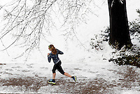 A runner runs through the snow in Downtown Charlottesville, VA. Photo/Andrew Shurtleff