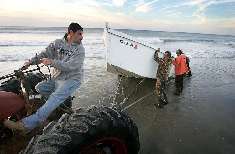 Chuck Beckley/        After setting the nets, the skif is hauled out of the surf by tractor and the wait for the fish to be brought in begins.