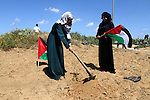 Palestinian women hold their national flags as they plant olive trees to mark Land Day during a symbolic ceremony held in the village of Abassan, east of Khan Yunis near the border fence between Israel and the southern Gaza Strip on March 31, 2015. On the annual Land Day, demonstrations are held to remember six Arab Israeli protesters who were shot dead by Israeli police and troops during mass protests in 1976 against plans to confiscate Arab land in the Galilee. Photo by Abed Rahim Khatib