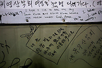 A pro unification message is left by the visitors of a small fishermen restaurant on the island of Baengnyeong that lays just inside the South Korean side of the Northern Limit Line (NLL) in Yellow Sea April 11, 2014. Despite the proximity of North Korea, numbers of tourists seem to enjoy the adventurous tours to security-sensitive zones. Baengnyeong, closer to Pyongyang than Seoul, is an isolated and heavily militarized island whose resident live in constant fear of possible clashes between two armies. The beaches of Baengnyeong are often walled with barbed wire fences straddling the sand dunes with intermittent holes for machine gun positions. The Northern Limit Line, a disputed maritime border that wraps itself round a part of the NorthÕs coastline, has been the scene of frequent clashes between South and North Korea. The line was drawn up at the end of the 1950-53 Korean War and North Korea does not recognize it. The two sides are still technically at war as the conflict ended in a mere truce, not a treaty.  Picture taken April 11, 2014. REUTERS/Damir Sagolj (SOUTH KOREA)