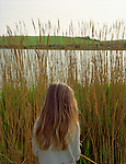Ten year old girl standing by a lake.