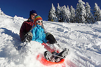 Mother and daughter sledding on snow in mountains, Hurricane Ridge, Clallam County, Olympic National Park, Washington, USA