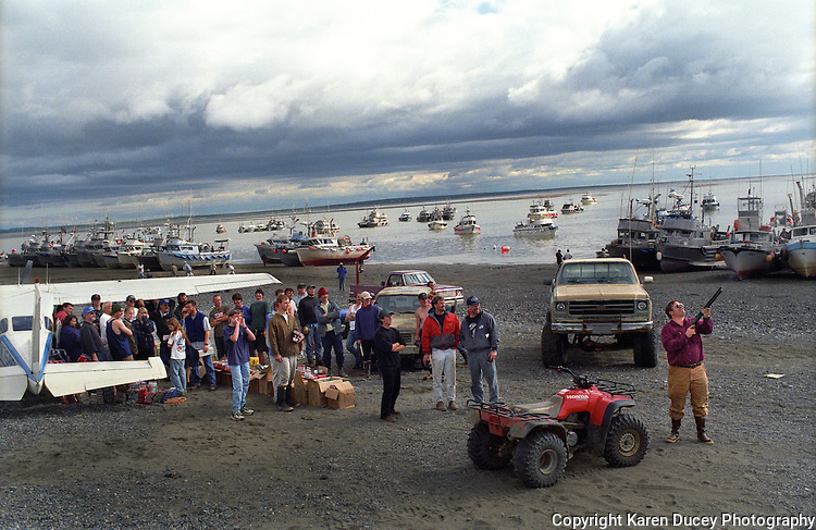 A person selling fireworks demonstrates one of the products he has for sale to fishermen after landing his plane on the beach in Coffee Point, Egegik, Alaska during a fishing closure in the Egegik River fishing district of Bristol Bay, Alaska in July 1993.  Bristol Bay is home to the world's largest sockeye salmon fishery.  The commercial salmon drift gillnet fishing fleet is limited to boats no longer than 32 feet in length.  There were over 1,800 permanent entry permits listed in 2002, required per boat.  Typically boats fish with two or three deckhands.  The fishery is managed by the Alaska Department of Fish & Game and is a sustainable fishery. Peak of the season is around July 4th in this fishery which lasts about a month. The rivers also get a fair amount of chum, king, and chinook salmon.  Bristol Bay is located in the southwest part of Alaska.