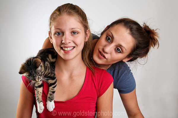 Two teenage girls (sisters) and their kitten.