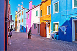 Brightly painted houses, each a different color line a street in Burano, Italy