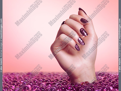 Woman hand with purple nail polish coming out of a sea of candy isolated on pink background