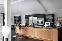 A long kitchen island with a green marble work top ending in a breakfast bar dominates this spectacular professional kitchen
