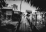 Young girl walks along elevated walkway connecting her neighborhood to a road that Tonle Sap never inundates, even at the height of the monsoon in Chong Kneas, Cambodia.
