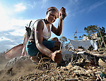A woman digs with a machete as she builds a temporary home in a spontaneous camp for quake survivors being established in Croix-des-Bouquets, Haiti, north of the capital Port-au-Prince. Quake survivors continue to move as aftershocks continue, and reports of aid deliveries in one camp will provoke families from other camps to migrate there.