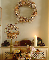 A wreath made of ribbons hangs above a wooden chest displaying a pile of Christmas presents beside a dish of mince pies