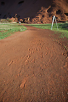 Footprints in the red soil left by walkers at the base of Uluru/Ayers Rock