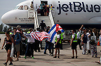 SANTA CLARA, CUBA - AUGUST 31 : Tourists with flags get off of Jet Blue plane of the first commercial flight between the US and Cuba during the arrival of  inaugural flight at Abel Santamaría Airport on August 31, 2016 in Santa Clara, Cuba. Photo by VIEWpress