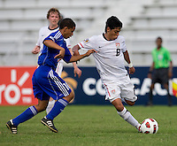 Esteban Rodriguez (9) of the United States passes the ball away from Frank Lopez (10) of Cuba during the first day of the group stage at the CONCACAF Men's Under 17 Championship at Catherine Hall Stadium in Montego Bay, Jamaica. The United States defeated Cuba, 3-1.