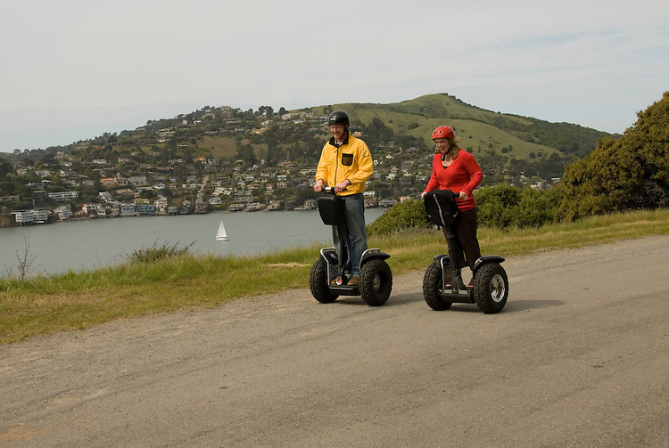 Couple on Segways, each on a Segway, on Angel Island State Park in San Francisco Bay, California, CA. Model released..Photo camari202-70410..Photo copyright Lee Foster, www.fostertravel.com, 510-549-2202, lee@fostertravel.com.