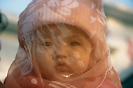 October 1984. Beijing on Sunday, face of young toddler, some are protected from the sun and flies with a small net.