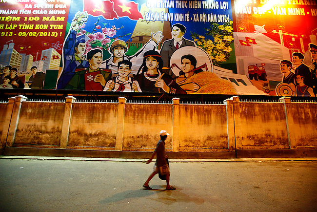 A man walks under a set of illuminated Communist propaganda posters in the Central Highlands town of Kon Tum, Vietnam. April 13, 2012.